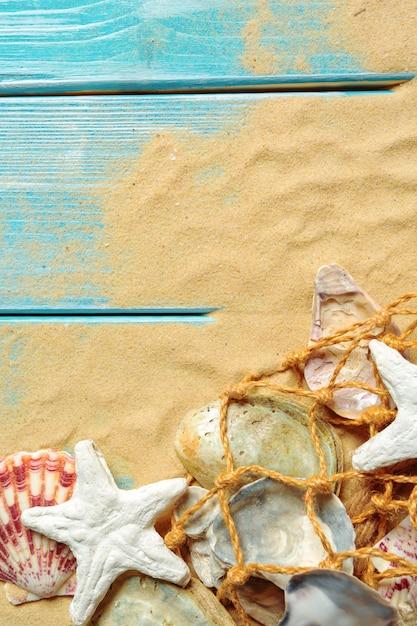 Corda del mare con molte conchiglie differenti sulla sabbia di mare su un fondo di legno blu. vista dall'alto Foto Premium