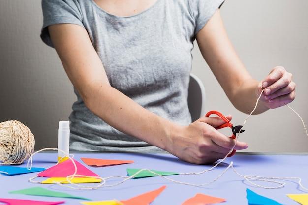 Corda di taglio manuale della donna con le forbici durante la fabbricazione della stamina Foto Gratuite
