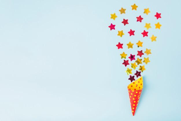 Coriandoli di forma stella che esce dal cono di carta con pois su sfondo blu Foto Gratuite