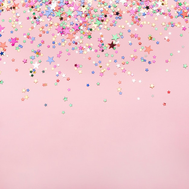 Coriandoli di stelle colorate su sfondo rosa con spazio di copia Foto Gratuite