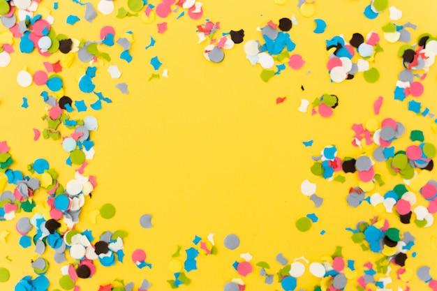 Coriandoli su sfondo giallo dopo aver terminato la festa Foto Gratuite