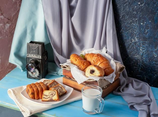 Cornetti con crema al cioccolato e un bicchiere di latte sul tavolo blu. Foto Gratuite