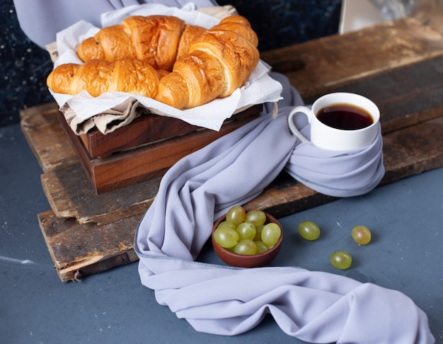 Cornetti e uva verde con una tazza di caffè espresso sul tavolo blu Foto Gratuite