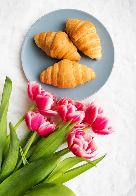 Cornetti sullo sfondo di lacci su uno sfondo bianco con un mazzo di tulipani rosa Foto Premium