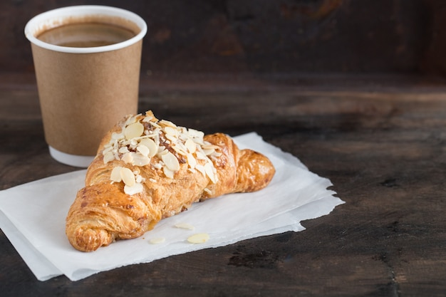 Cornetto e caffè freschi in una tazza di carta Foto Premium