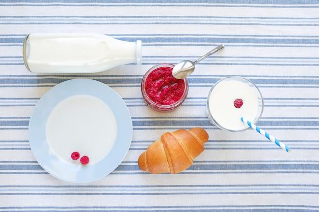 Cornetto, piatto, marmellata di lamponi in un barattolo, latte in un bicchiere e una bottiglia su un asciugamano di lino. Foto Premium