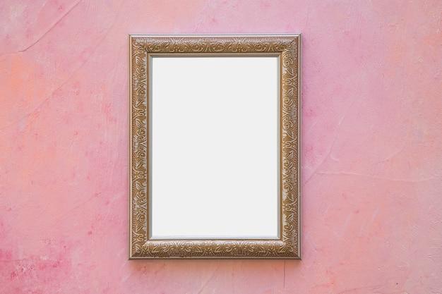 Cornice bianca ornata d'oro sulla parete rosa Foto Gratuite