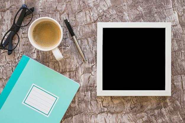 Cornice bianca; tazza di caffè; occhiali; penna e quaderno su sfondo strutturato Foto Gratuite