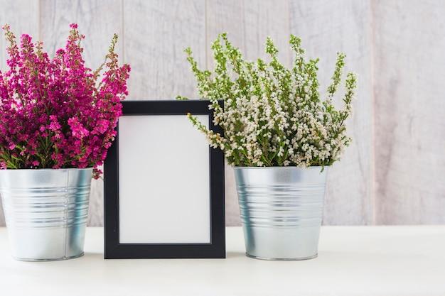 Cornice bianca tra i fiori rosa e bianchi in una pentola di alluminio Foto Gratuite