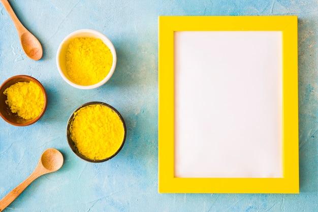 Cornice bianca vuota con bordo giallo vicino alla polvere di colore holi su sfondo concreto Foto Gratuite