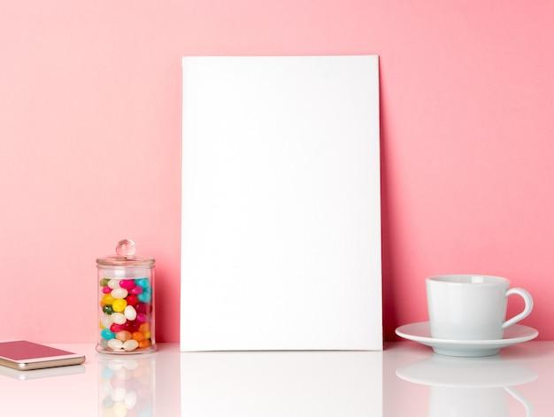 Cornice bianca vuota e candys in barattolo, tazza di caffè o tè su un tavolo bianco contro il muro rosa Foto Premium