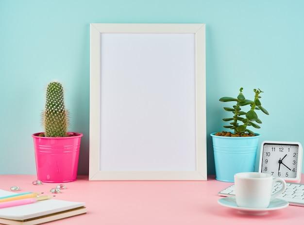 Cornice bianca vuota mockup, allarme, blocco note, tazza di caffè o tè sul tavolo rosa Foto Premium