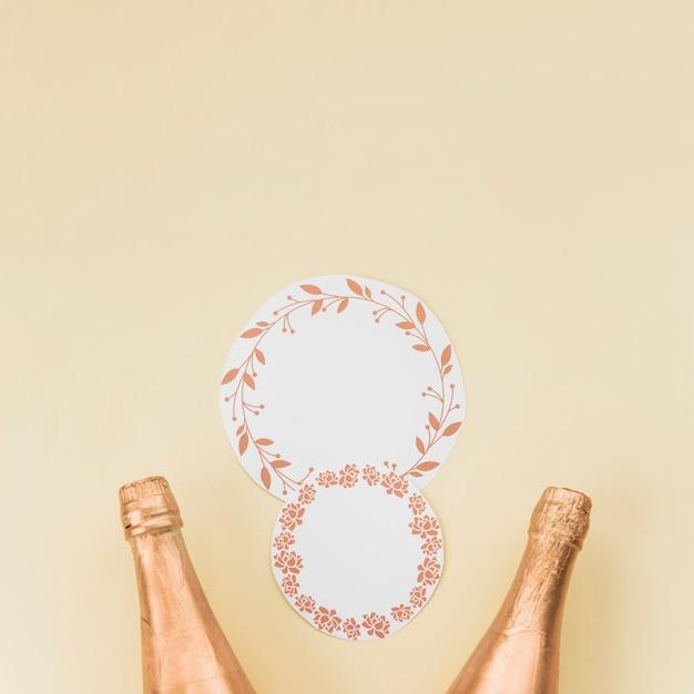 Cornice circolare con foglie e motivi floreali vicino a due bottiglie di champagne sul fondale beige Foto Gratuite