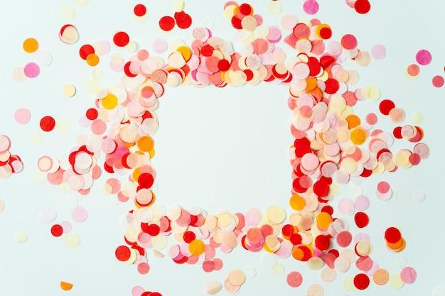 Cornice colorata fatta con coriandoli festivi rosso e arancione su sfondo pastello Foto Premium