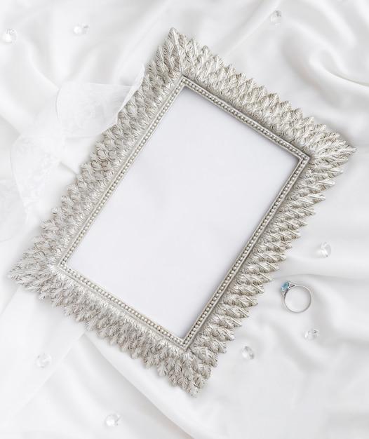 Cornice con anello di fidanzamento a fianco Foto Gratuite