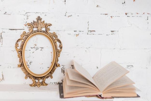 Cornice d'epoca ornato e un libro aperto contro il muro bianco Foto Gratuite