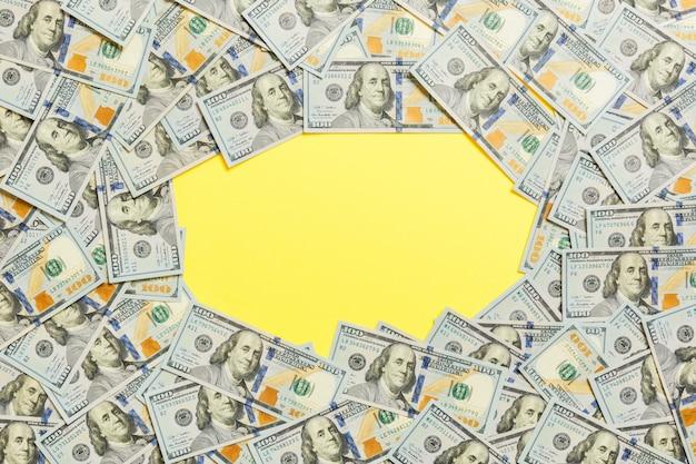Cornice di banconote da cento dollari. vista dall'alto del concetto di business su sfondo giallo Foto Premium