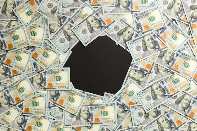 Cornice di banconote da cento dollari. vista dall'alto del concetto di business su sfondo nero con spazio di copia Foto Premium