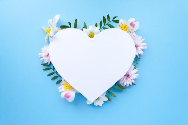 Cornice di camomille, rami, foglie e petali lilla su sfondo blu. vista piana, vista dall'alto Foto Premium