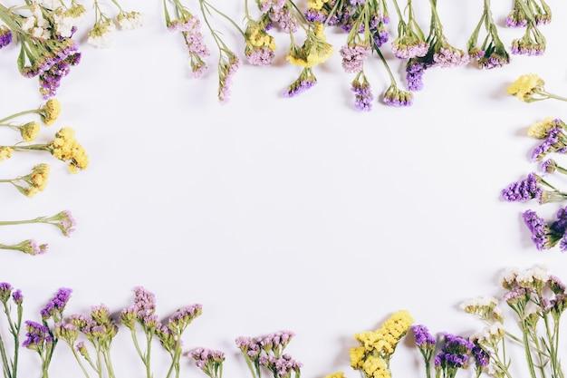 Cornice di fiori colorati su uno sfondo bianco Foto Premium