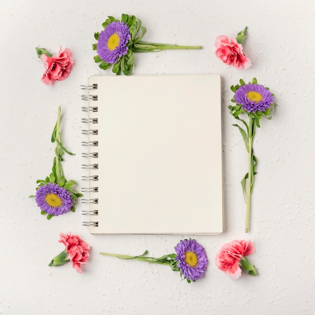 Cornice di fiori viola e garofano naturale con blocco note Foto Gratuite