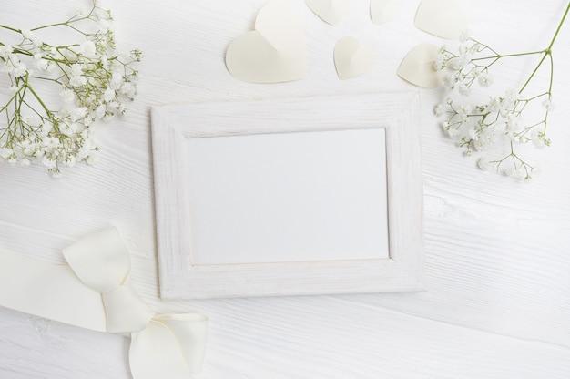Cornice di mockup con fiori e biglietto di auguri di prua Foto Premium