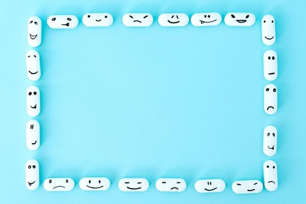 Cornice di pillole con facce buffe su sfondo blu Foto Premium
