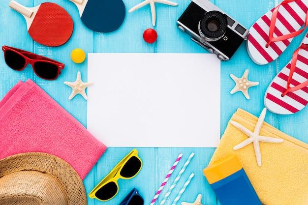 Cornice di sfondo estivo, carta bianca, spiaggia di sandalo, cappello, stelle marine su legno blu Foto Gratuite