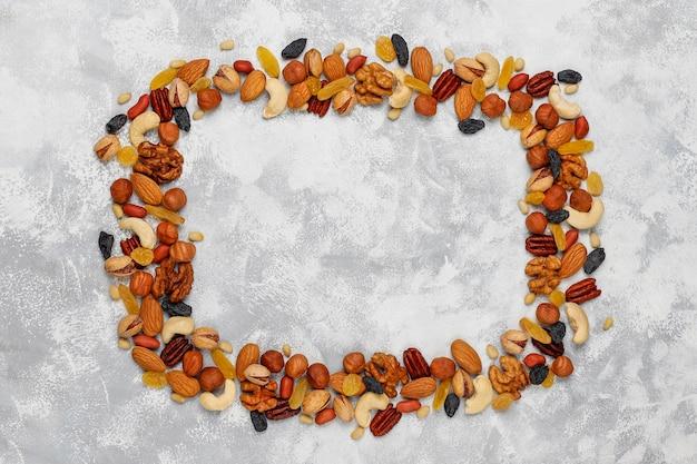 Cornice di vari tipi di noci, anacardi, nocciole, noci, pistacchi, noci pecan, pinoli, arachidi, uvetta. vista dall'alto Foto Gratuite