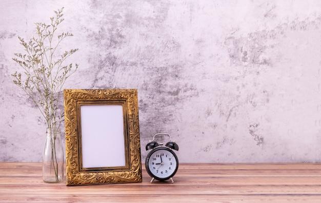 Cornice e fiori ed orologio sulla tavola di legno Foto Premium