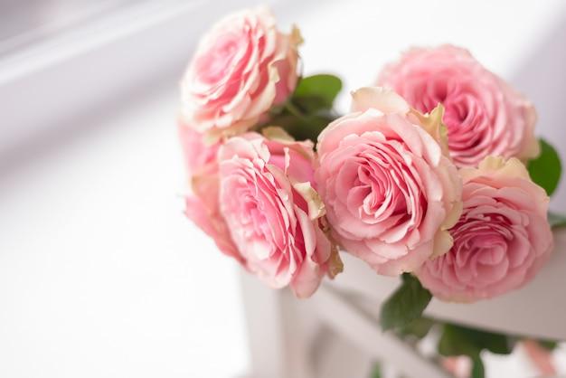Cornice floreale carta delicata con rose rosa su uno sfondo bianco e rosa morbido. spazio per il testo. Foto Premium