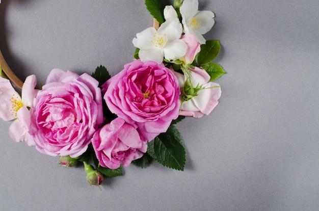 Cornice floreale fiori di rosa su uno sfondo grigio. distesi Foto Premium