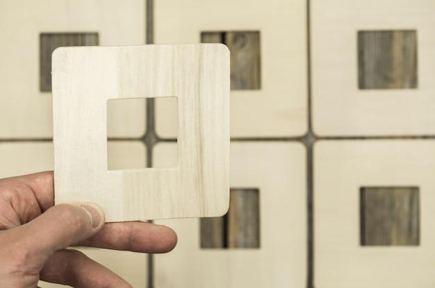 Cornice in legno su e un fotogramma nella mano maschile, primo piano Foto Gratuite