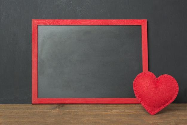 Cornice lavagna con posto per il testo e cuore di feltro rosso come decorazione sul tavolo di legno. carta di san valentino. . Foto Premium