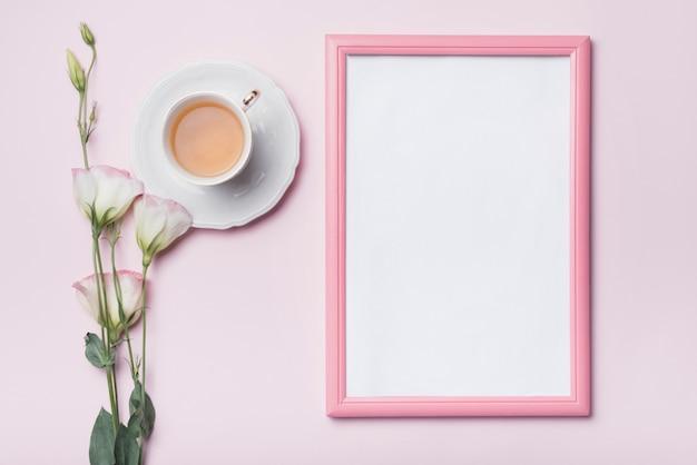 Cornice per foto in bianco con bordo rosa; tazza di tè e fiori freschi di eustoma su sfondo colorato Foto Gratuite