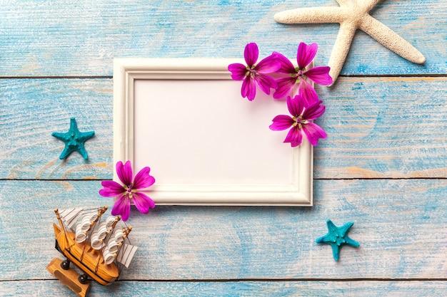 Cornice per foto in legno bianco con fiori viola su sfondo blu vecchio malandato con spazio di copia. Foto Premium