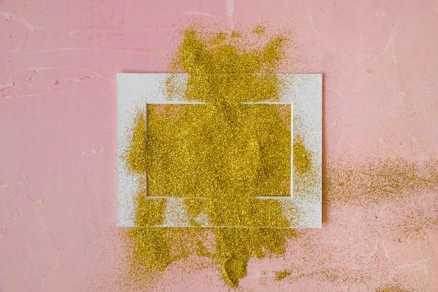 Cornice ricoperta di paillettes gialle sul tavolo rosa Foto Gratuite