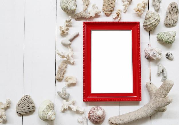 Cornice rossa in legno su un pavimento di legno bianco e conchiglie e barriere coralline. Foto Premium