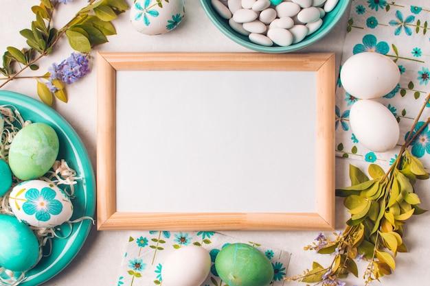 Cornice tra le uova di pasqua sul piatto vicino a piccole pietre in ciotola e ramoscelli di fiori Foto Gratuite