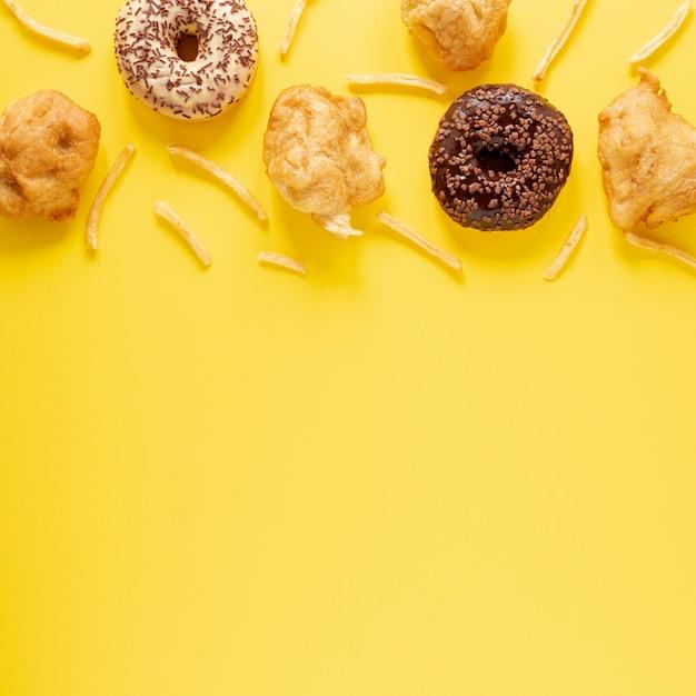 Cornice vista dall'alto con ciambelle e sfondo giallo Foto Gratuite