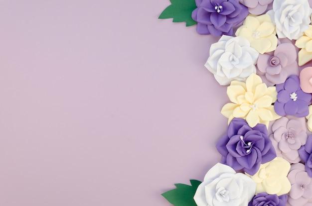 Cornice vista dall'alto con fiori di carta su sfondo viola Foto Gratuite