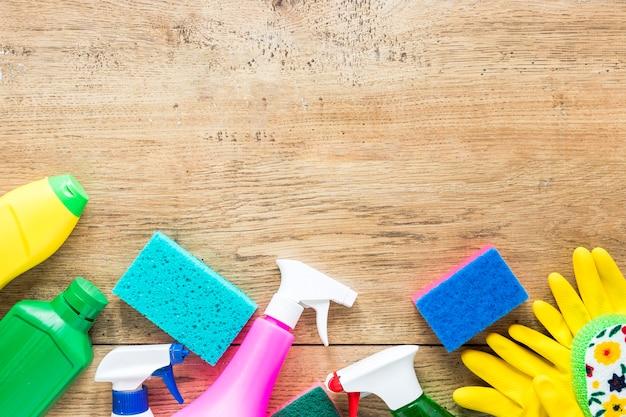 Cornice vista dall'alto con prodotti per la pulizia e fondo in legno Foto Gratuite