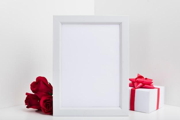 Cornice vuota con scatola regalo e rose rosse Foto Gratuite