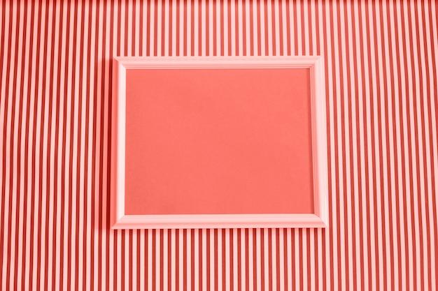 Cornice vuota mock up su sfondo a strisce bianco e corallo. Foto Premium