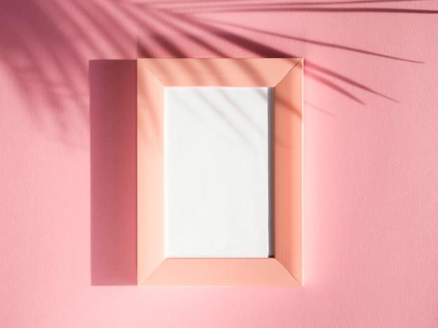 Cornici per ritratto rosa su uno sfondo rosa con un'ombra di foglia di palma Foto Gratuite