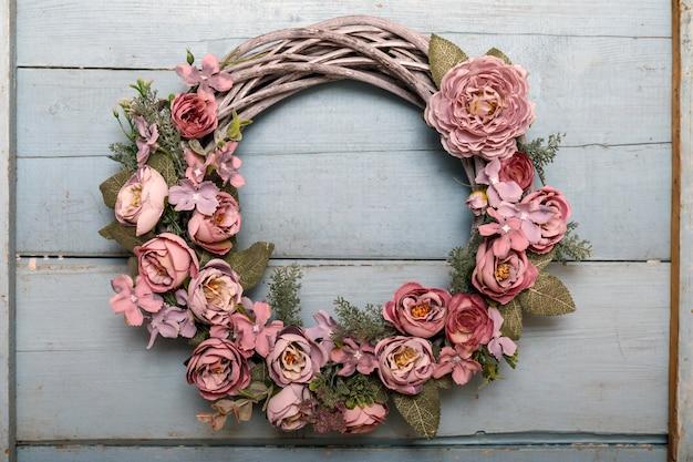 Corona d'annata di autunno dalle foglie e dai fiori sul legno di shabbi Foto Premium