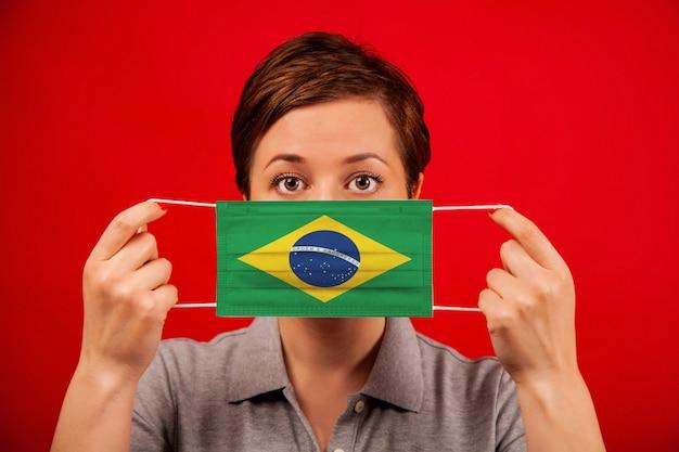 Coronavirus covid-19 in brasile. donna in maschera protettiva medica con l'immagine della bandiera brasiliana. Foto Premium