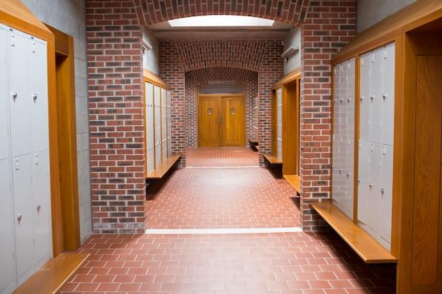 Corridoio di muro di mattoni con pavimento piastrellato in un