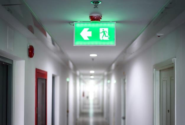 Corridoio in appartamento con stanze della porta con il segnale luminoso verde dell'uscita di sicurezza Foto Premium