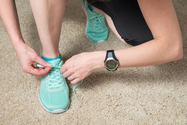 Corridore che allaccia i lacci indossando monitor della frequenza cardiaca e tracker di attività per esercizi cardio Foto Premium